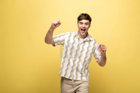 Photo for Happy man showing winner gesture while smiling at camera on yellow background - Royalty Free Image