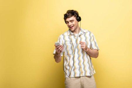 Photo pour Jeune homme gai écoutant la musique dans des écouteurs et utilisant le smartphone sur le fond jaune - image libre de droit