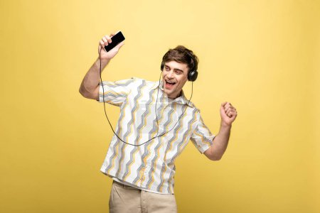 Photo for Cheerful young man dancing while listening music with headphones and smartphone on yellow background - Royalty Free Image