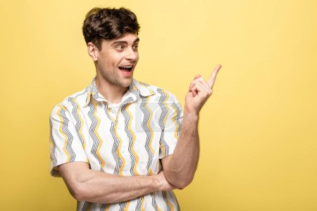 Photo for Cheerful young man looking pointing with finger while looking away on yellow background - Royalty Free Image