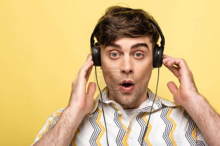 Photo for Shocked young man looking at camera while listening music in headphones isolated on yellow - Royalty Free Image