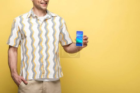 Photo for Cropped view of smiling man showing smartphone with booking app, isolated on yellow - Royalty Free Image