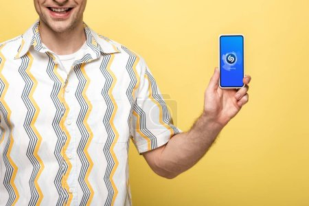 Photo for KYIV, UKRAINE - MAY 16, 2019: cropped view of smiling man showing smartphone with shazam app, isolated on yellow - Royalty Free Image
