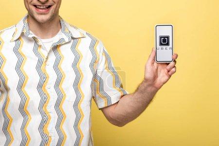 Photo pour Kiev, Ukraine - 16 mai 2019: vue recadrée d'homme souriant montrant smartphone avec l'application uber, isolé sur le jaune - image libre de droit