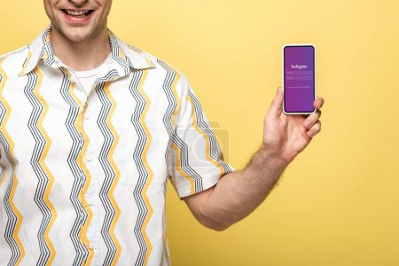 Photo for KYIV, UKRAINE - MAY 16, 2019: cropped view of smiling man showing smartphone with instagram app, isolated on yellow - Royalty Free Image