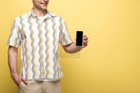 Photo for Cropped view of young man holding smartphone with blank screen on yellow background - Royalty Free Image