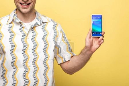 cropped view of smiling man showing smartphone with booking app, isolated on yellow