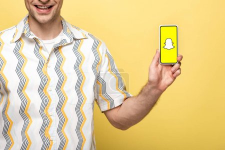 Photo for KYIV, UKRAINE - MAY 16, 2019: cropped view of smiling man showing smartphone with Snapchat app, isolated on yellow - Royalty Free Image