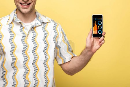 Photo for Cropped view of smiling man showing smartphone with infographic, isolated on yellow - Royalty Free Image