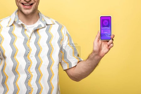 Photo for Cropped view of smiling man showing smartphone with shopping app, isolated on yellow - Royalty Free Image