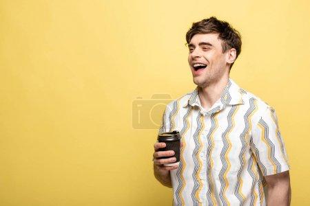 Photo pour Homme heureux regardant loin tout en retenant la tasse jetable sur le fond jaune - image libre de droit