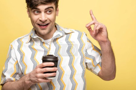 Photo for Cheerful young man holding paper cup and showing idea sign while looking away on yellow background - Royalty Free Image