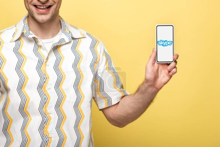 Photo pour KYIV, UKRAINE - MAY 16, 2019: cropped view of smiling man showing smartphone with skype app, isolated on yellow - image libre de droit
