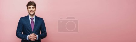 Foto de Panoramic shot of handsome, cheerful businessman smiling at camera on pink background - Imagen libre de derechos