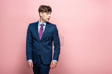 Photo pour Homme d'affaires pensif dans le procès regardant loin sur le fond rose - image libre de droit