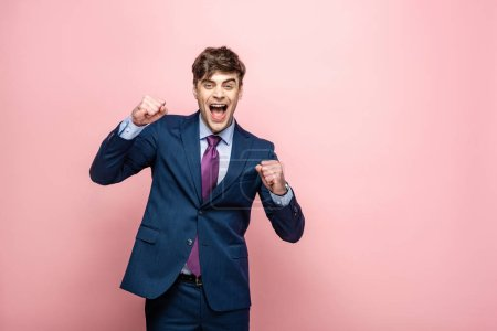 Photo for Cheerful businessman showing winner gesture while looking at camera on pink background - Royalty Free Image