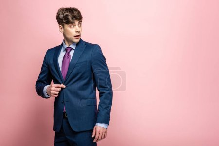 Photo for Handsome, surprised businessman in suit looking away on pink background - Royalty Free Image