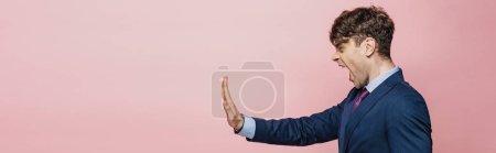 Photo pour Tir panoramique de l'homme d'affaires fâché affichant le geste d'arrêt d'isolement sur le rose - image libre de droit