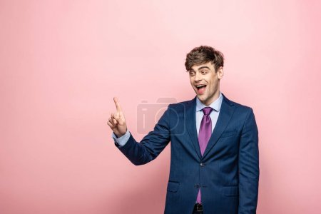 Photo for Cheerful businessman looking away and showing idea gesture on pink background - Royalty Free Image