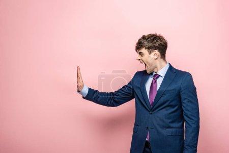 Photo pour Homme d'affaires irrité affichant le geste d'arrêt tout en regardant loin sur le fond rose - image libre de droit