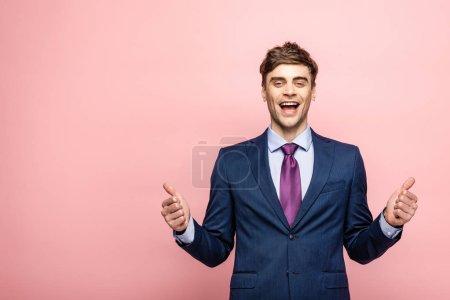 Photo pour Bel homme d'affaires souriant à la caméra et montrant pouces vers le haut sur fond rose - image libre de droit