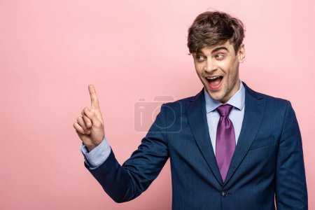 Photo for Cheerful businessman showing idea sign while looking away on pink background - Royalty Free Image
