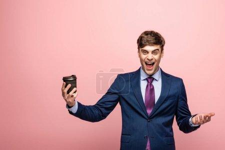 Photo pour Homme d'affaires excité retenant le café pour aller tout en riant à l'appareil-photo sur le fond rose - image libre de droit