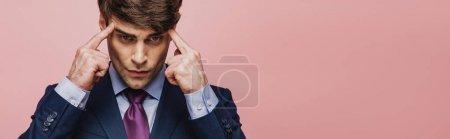 Photo pour Plan panoramique de l'homme réfléchi touchant la tête avec les doigts isolés sur rose - image libre de droit