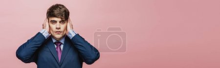 Photo for Panoramic shot of serious businessman covering ears with hands isolated on pink - Royalty Free Image