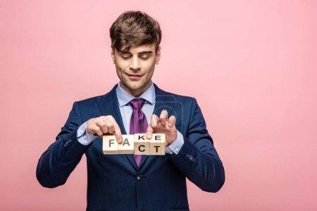 Photo pour Homme souriant tenant des cubes en bois avec inscription faux fait isolé sur rose - image libre de droit