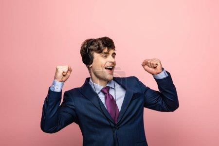 Photo pour Homme d'affaires excité dansant tout en écoutant la musique dans des écouteurs sur le fond rose - image libre de droit