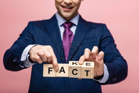 Photo pour Vue recadrée de l'homme d'affaires tenant des cubes en bois avec un faux lettrage sur fond rose - image libre de droit