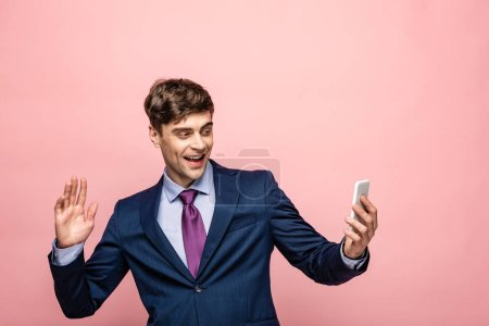 Photo for Smiling businessman waving hand during video chat in smartphone isolated on pink - Royalty Free Image