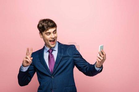 Photo pour Homme d'affaires gai affichant le geste de victoire tout en utilisant le smartphone sur le fond rose - image libre de droit