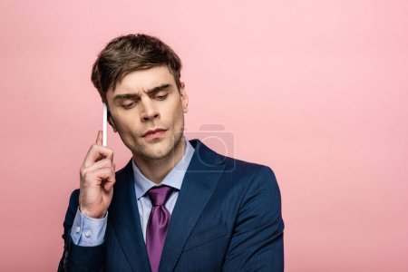 Photo for Thoughtful businessman in formal wear talking on smartphone isolated on pink - Royalty Free Image