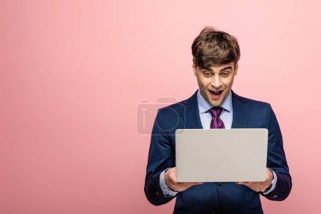 Foto de Alegre hombre de negocios en ropa formal mirando portátil sobre fondo rosa - Imagen libre de derechos
