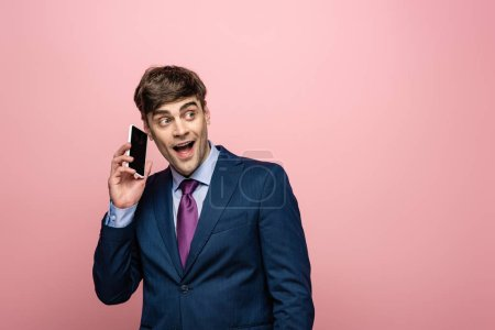 Photo for Positive businessman talking on smartphone and looking away on pink background - Royalty Free Image