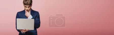 Foto de Plano panorámico de empresario reflexivo utilizando el ordenador portátil sobre fondo rosa - Imagen libre de derechos