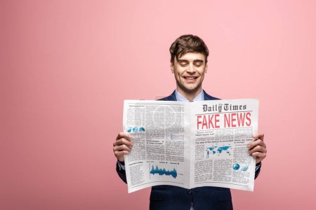 Photo for Cheerful businessman reading newspaper with fake news and smiling on pink background - Royalty Free Image