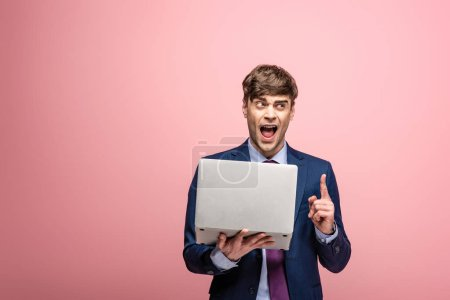 Photo for Excited businessman showing idea gesture while holding laptop on pink background - Royalty Free Image