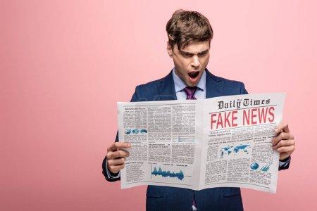Photo pour Choqué homme d'affaires lecture journal avec de fausses nouvelles sur fond rose - image libre de droit