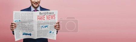 Photo pour Vue recadrée d'un homme d'affaires souriant lisant un journal avec de fausses nouvelles sur fond rose, plan panoramique - image libre de droit