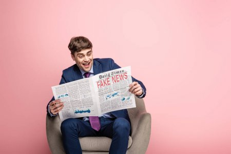 Photo for Cheerful businessman sitting in armchair and reading newspaper with fake news on pink background - Royalty Free Image