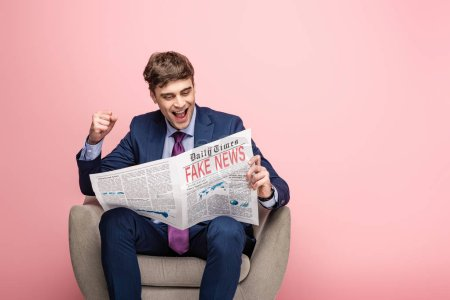 Photo for Cheerful businessman showing winner gesture while sitting in armchair and reading newspaper with fake news on pink background - Royalty Free Image