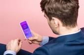 """Постер, картина, фотообои """"обрезанный вид бизнесмена с помощью смартфона с приложением для покупок, изолированных на розовый"""""""