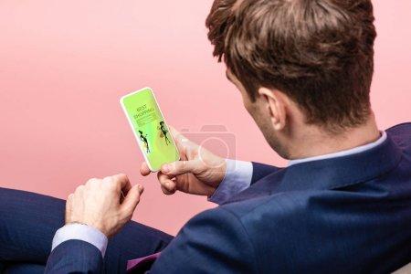 Photo pour Vue recadrée de l'homme d'affaires à l'aide d'un smartphone avec la meilleure application shopping, isolé sur rose - image libre de droit