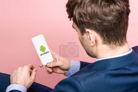 Photo for KYIV, UKRAINE - MAY 16, 2019: cropped view of businessman using smartphone with android app, isolated on pink - Royalty Free Image