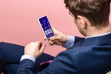 Foto de Cropped view of businessman using smartphone with health app, isolated on pink - Imagen libre de derechos