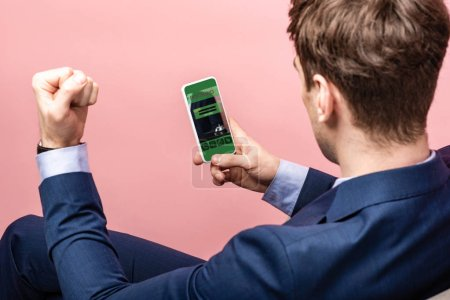 Photo for Cropped view of successful businessman using smartphone with booking app, isolated on pink - Royalty Free Image