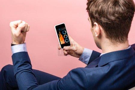 Photo pour Vue recadrée de l'homme d'affaires réussi utilisant le smartphone avec l'infographie, d'isolement sur le rose - image libre de droit